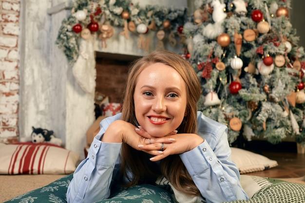 Красивая молодая женщина в канун рождества, лежит перед камином с елкой и новогодним декором и мечтами. рождественские желания сбудутся. Premium Фотографии