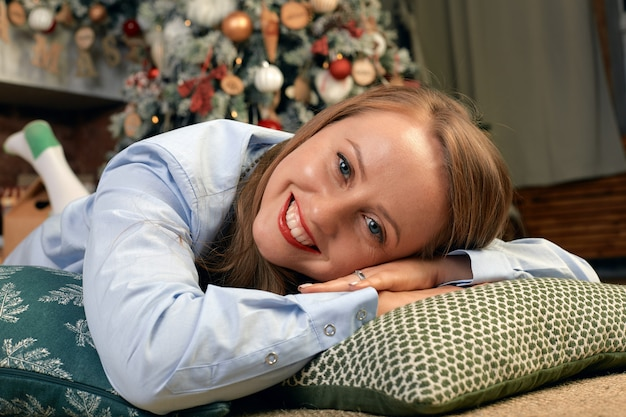 Красивая молодая женщина в канун рождества, лежит перед камином с елкой и новогодним декором и мечтами. концепция рождественские пожелания сбываются. Premium Фотографии