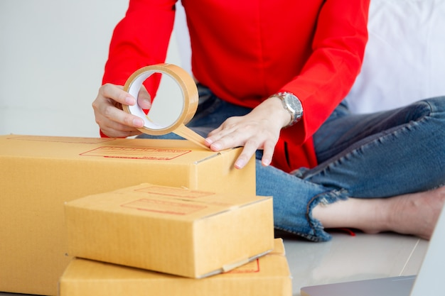 Beautiful young woman packing a parcel boxes.  e-commerce and start up business concept. Premium Photo