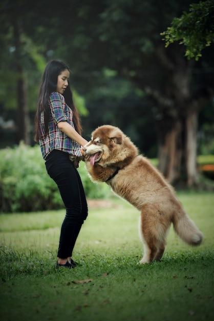 屋外の公園で彼女の小さな犬と遊ぶ美しい若い女性。ライフスタイルの肖像画。 無料写真