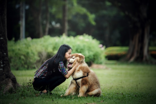 Beautiful young woman playing with her little dog in a park outdoors. lifestyle portrait. Free Photo