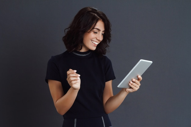 Beautiful young woman posing over grey wall and holding tablet in hands Free Photo