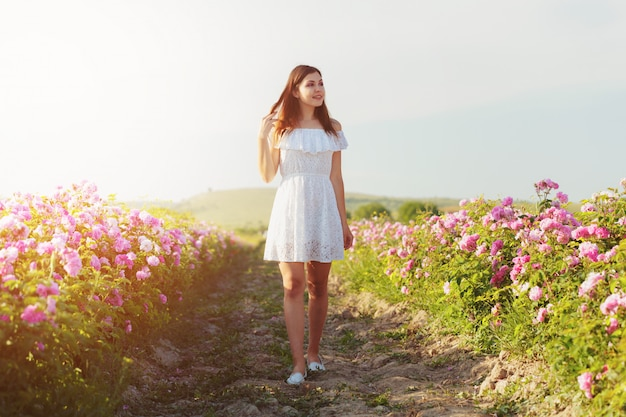 Beautiful young woman posing near roses in a garden, Premium Photo