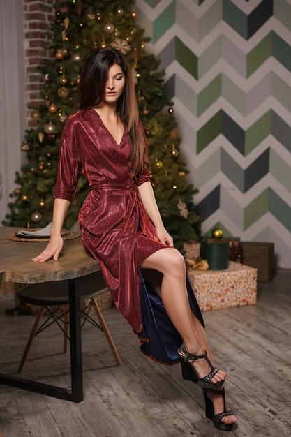 Beautiful young woman posing near the table Premium Photo