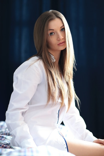 Красивая молодая женщина позирует с мужской рубашкой в постели Бесплатные Фотографии