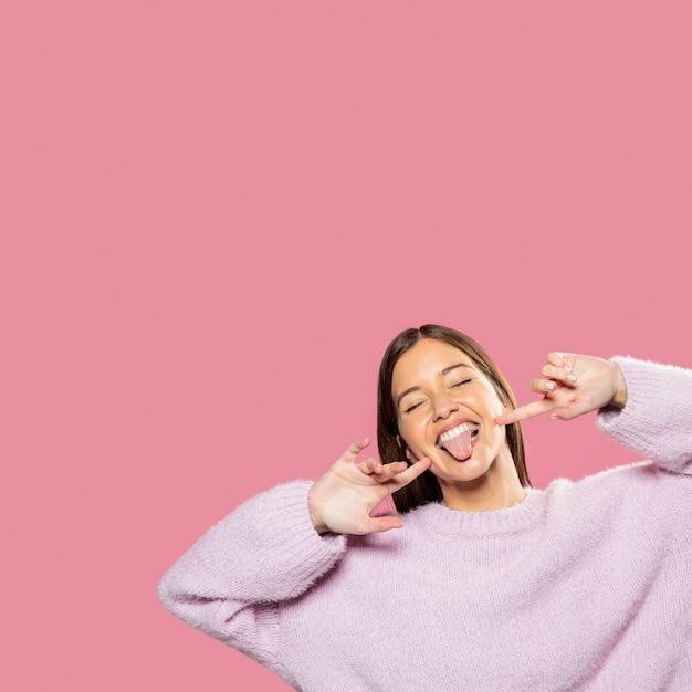 Красивая молодая женщина позирует с розовыми обоями в спине Бесплатные Фотографии