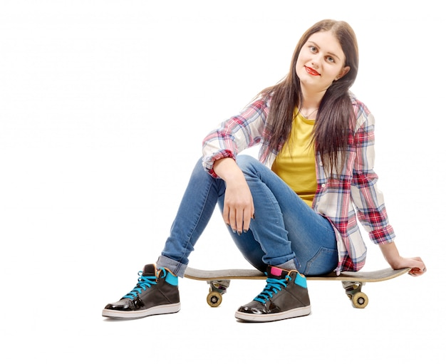 Beautiful young woman posing with a skateboard, seat on skate Premium Photo