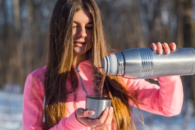 Beautiful young woman pours tea Premium Photo