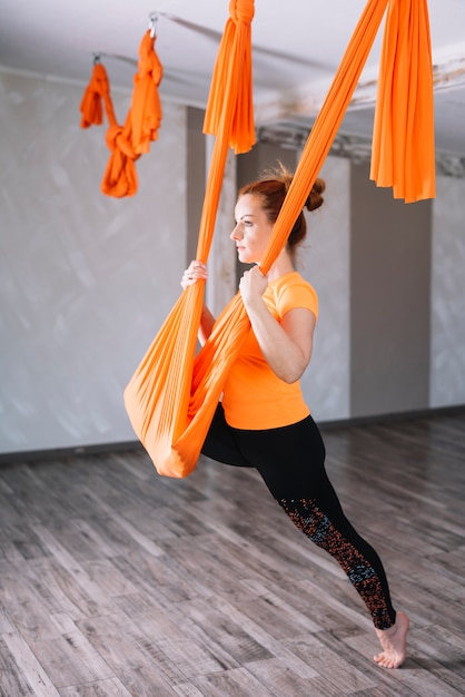 Beautiful young woman practicing aerial yoga in gym Free Photo