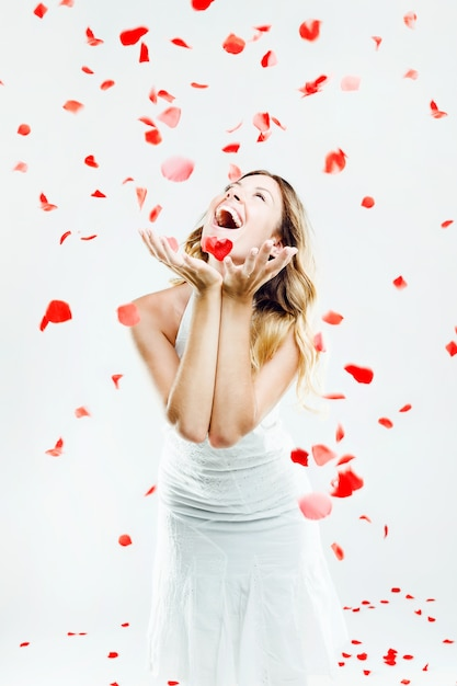 Beautiful young woman under a rain of rose petals. isolated on white. Free Photo