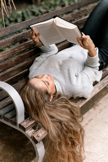 Beautiful young woman reading a book on a bench Free Photo