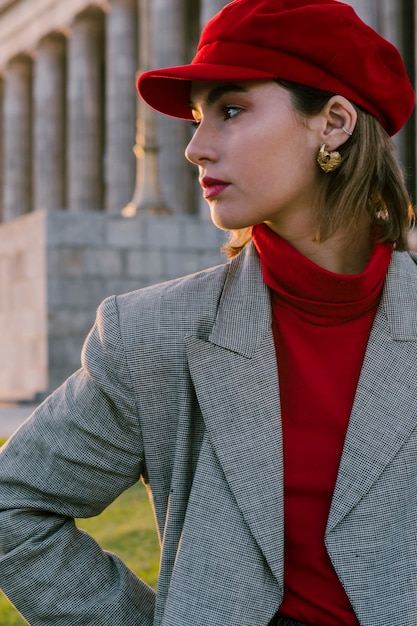 Beautiful young woman in red cap with golden earring in her ears looking away Free Photo