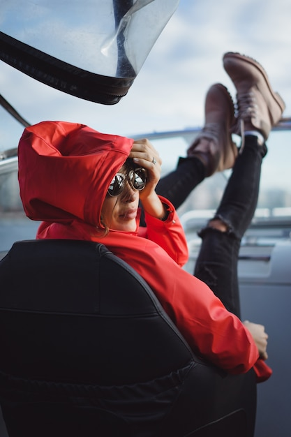 Beautiful young woman in a red raincoat rides a private yacht. stockholm, sweden Free Photo