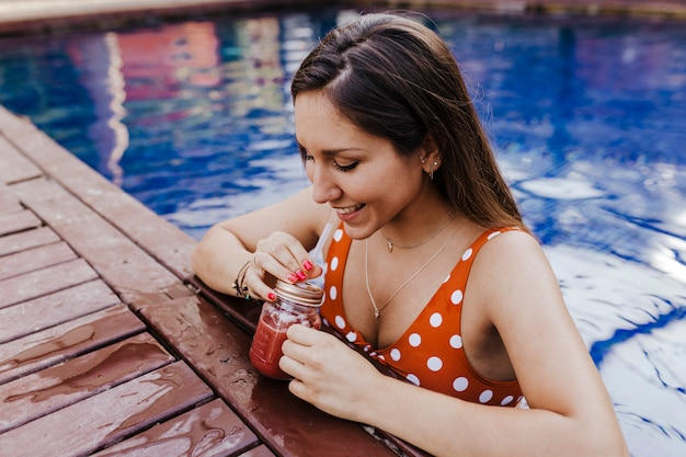 Beautiful young woman relaxing at the pool. holding a healthy juice and relaxing summer time and lifestyle Premium Photo