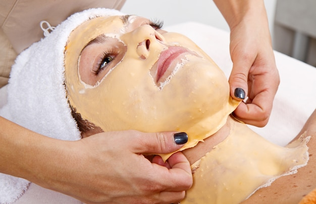 Beautiful young woman remove  facial mask  in a beauty center Premium Photo