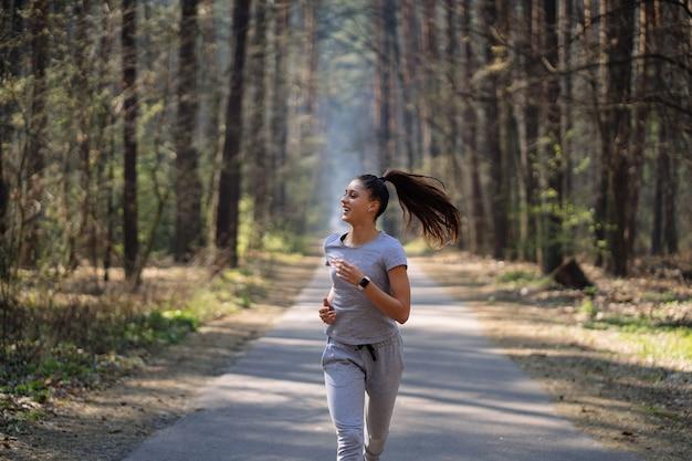 Красивая молодая женщина работает в зеленом парке в солнечный летний день Бесплатные Фотографии