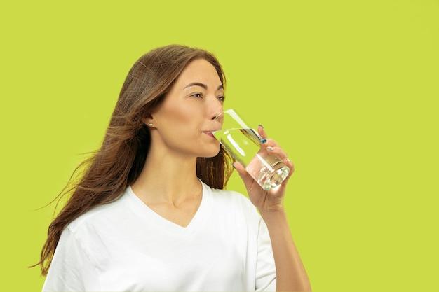 Поясной портрет красивой молодой женщины изолирован. женская модель выглядит счастливой и пьет воду. выражение лица, концепция человеческих эмоций, красота и здравоохранение. Бесплатные Фотографии