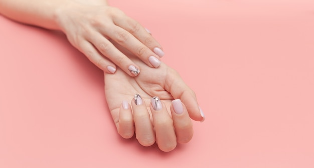 Beautiful young woman's hand with perfect manicure on pink Premium Photo