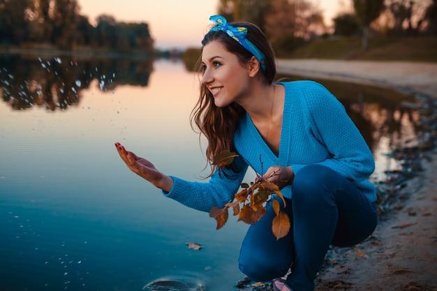Beautiful young woman sitting at autumn river bank splashing water Premium Photo