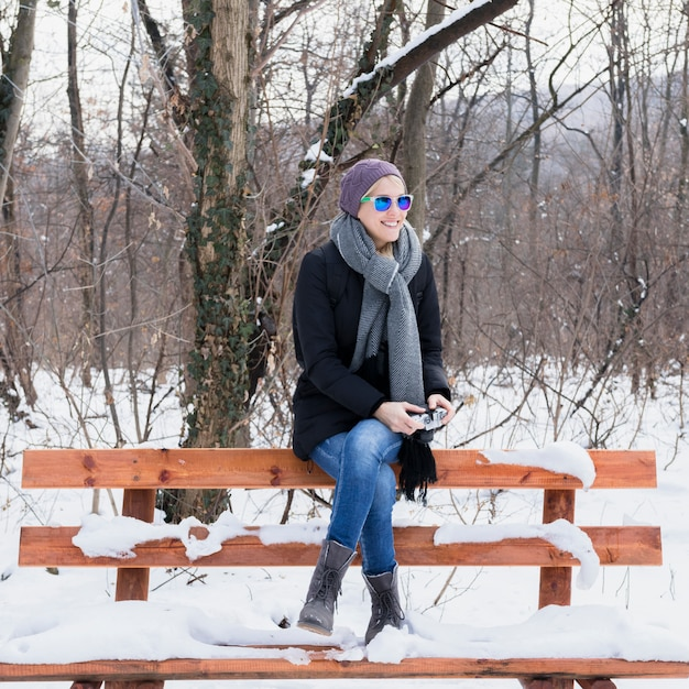 Beautiful young woman sitting bench with snow Free Photo
