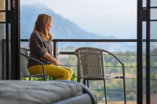 Beautiful young woman sitting on hotel balcony of the bedroom to enjoying sunrise landscape view. Premium Photo