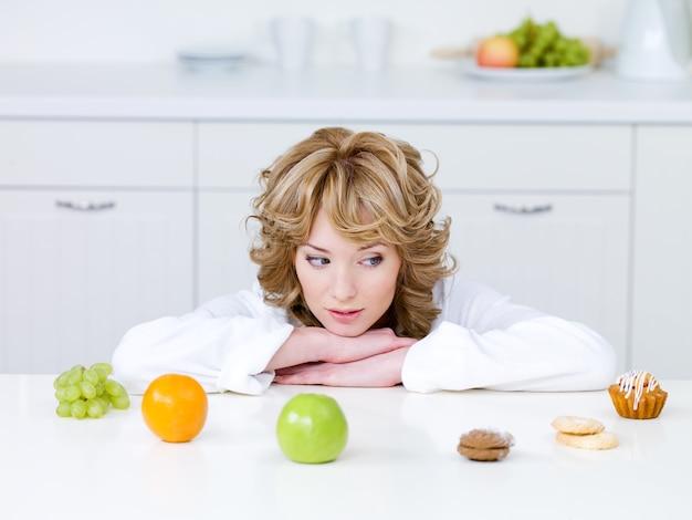 Красивая молодая женщина сидит на кухне и выбирает между полезными фруктами и вкусными пирожными Бесплатные Фотографии