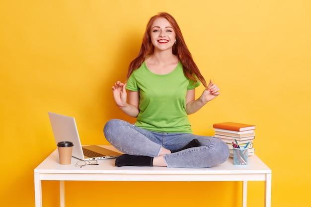 Bella giovane donna seduta al tavolo con le gambe incrociate vicino al lap top bianco, abiti femminili accattivanti maglietta casual e jeans, guardando sorridente alla fotocamera Foto Gratuite