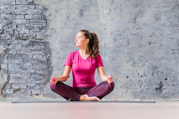 Beautiful young woman sitting in yoga position meditating Free Photo