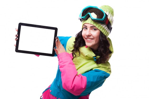 Beautiful young woman in ski outfit and ski goggles hold empty tablet Premium Photo
