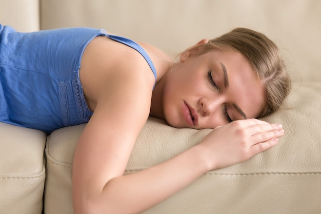 Beautiful young woman sleeping on couch at home, headshot portrait Free Photo
