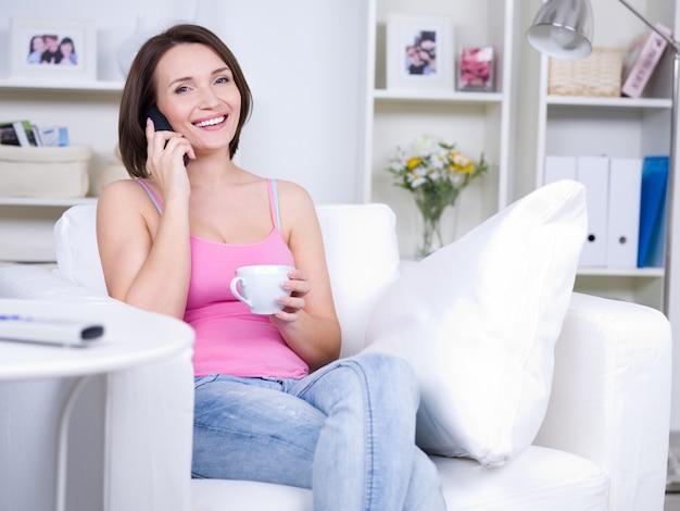 집에서 전화로 말하는 아름 다운 젊은 여자-실내 무료 사진