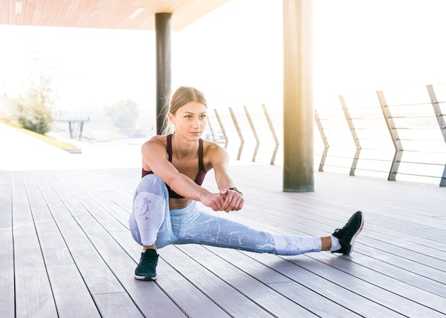 Beautiful young woman in sportswear doing stretching exercise Free Photo