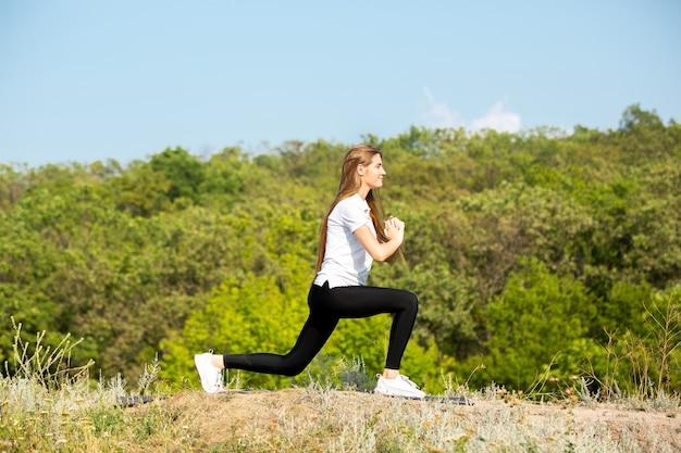 Bella giovane donna in abbigliamento sportivo allenamento all'aperto sul prato verde Foto Gratuite
