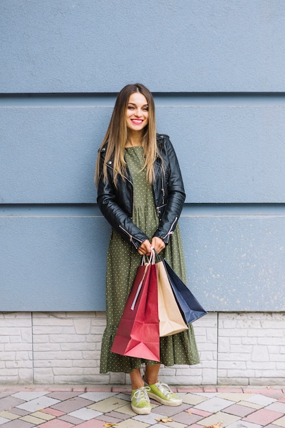 Beautiful young woman standing in front of wall holding colorful shopping bags Free Photo