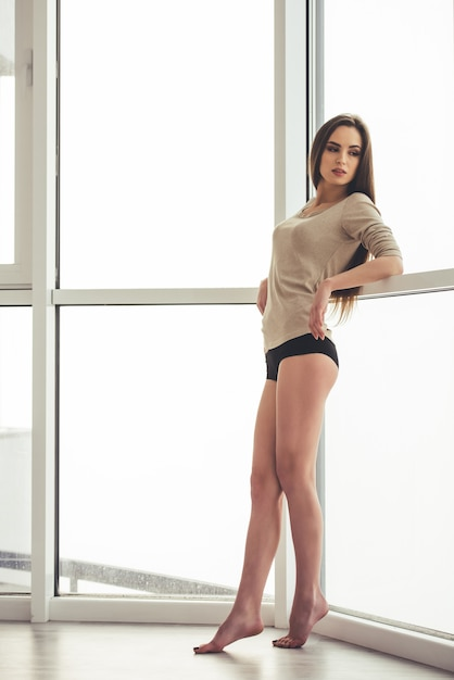 Beautiful young woman standing near the window. Premium Photo