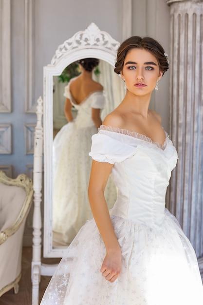 Beautiful young woman standing in white dress near mirror. Premium Photo