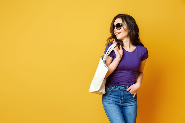 Beautiful young woman in sunglasses, purple shirt, blue jeans posing with bag on yellow background Premium Photo