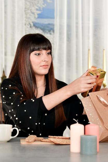 焦点が合っていない背景のテーブルに座っている紙袋からギフトボックスを取り出して美しい若い女性。 無料写真