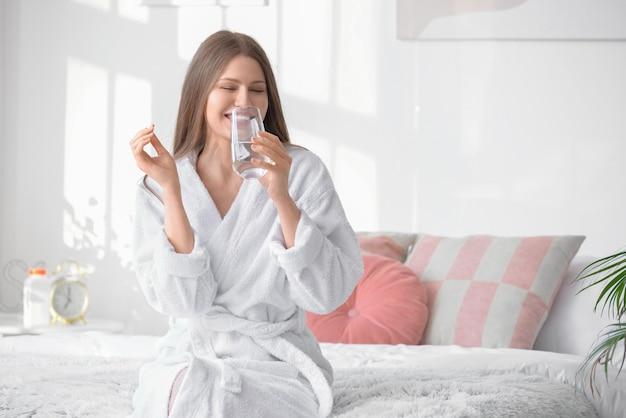 집에서 약을 복용하는 아름 다운 젊은 여자 프리미엄 사진