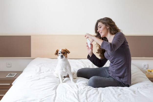 Beautiful young woman taking a selfie with mobile phone on bed with her cute small dog besides. home, indoors and lifestyle Premium Photo