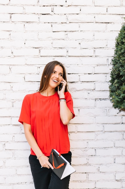 Beautiful young woman talking on cellphone in front of brick wall Free Photo