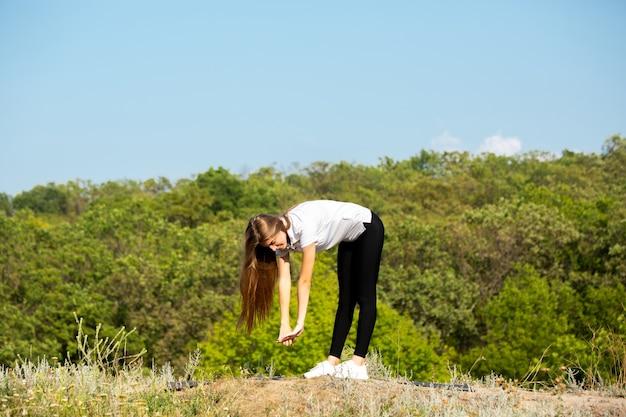 Bella giovane donna formazione flessibilità all'aperto Foto Gratuite