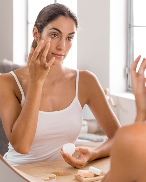 Красивая молодая женщина, используя дневной крем дома Premium Фотографии