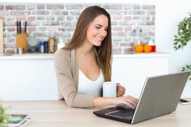 Beautiful young woman using her laptop in the kitchen. Free Photo