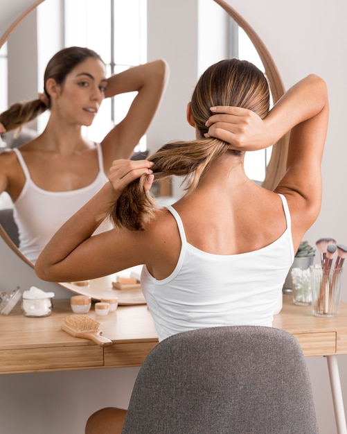 Красивая молодая женщина, используя продукты и глядя в зеркало Premium Фотографии