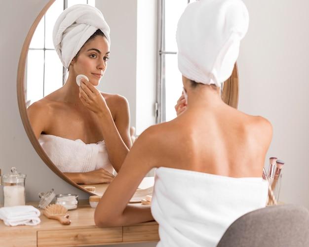 Красивая молодая женщина, используя продукты и глядя в зеркало Бесплатные Фотографии