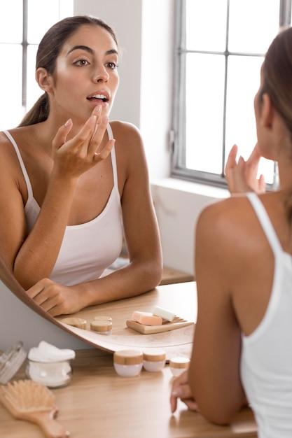Красивая молодая женщина, использующая спа-продукты дома Premium Фотографии
