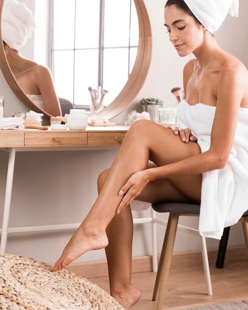 Красивая молодая женщина, использующая спа-продукты дома Бесплатные Фотографии