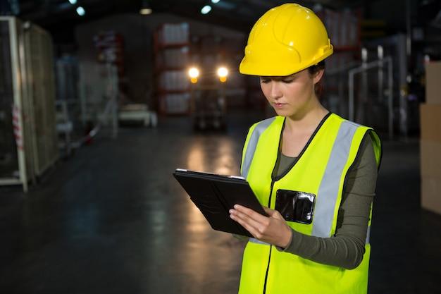 工場でタブレットpcを使用して美しい若い女性 無料写真