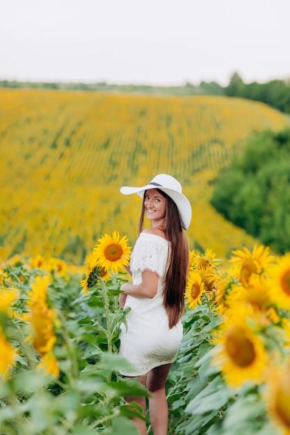 Красивая молодая женщина, ходить в поле цветущих подсолнухов в летнее время. стильная женщина с длинными волосами в белом платье и шляпе. летний отпуск Premium Фотографии